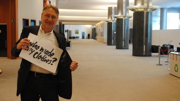"""Bernd Lange hält ein Schild hoch, auf dem steht: """"Who made my clothes?"""""""