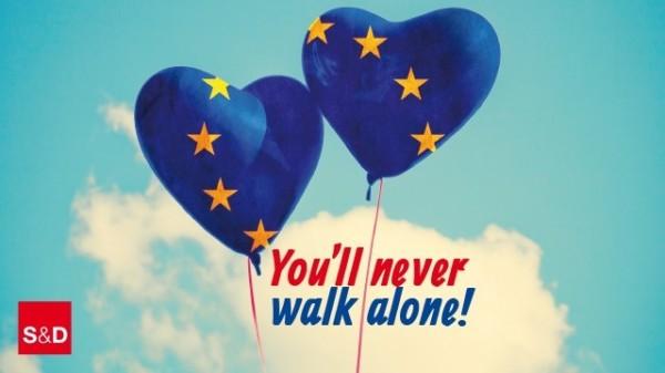 Zwei aufsteigende Luftballons in Europablau mit goldenen Sternen. Darunter der Schriftzug in Rot und Blau: You will never walk alone!